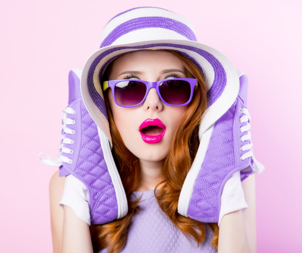quirky red-haired woman with sneakers on her hands