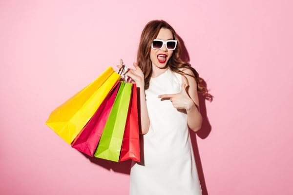 Photo of a pretty young brunette woman in white summer dress wearing sunglasses posing with shopping bags and looking aside over pink background