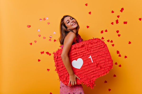 woman smiling holding an Instagram heart