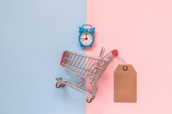 mini shopping car with shopping tag on pink and blue backdrop