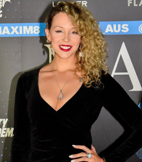 angela smiling on the red carpet with maxim in the background