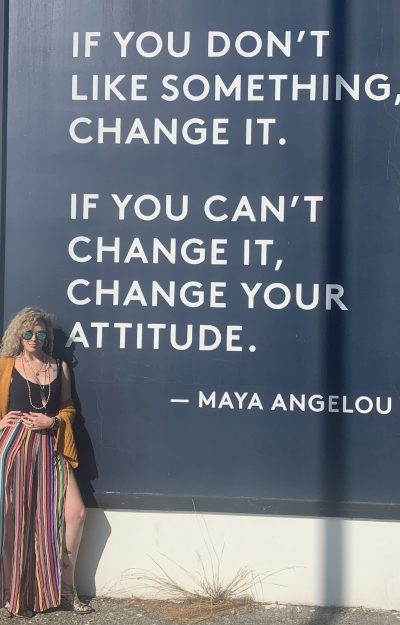 angela standing in front of a maya angelou quote in venice California