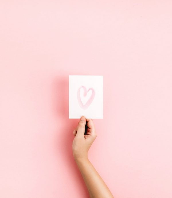 hand holding a white card with a love heart on it on a pink background